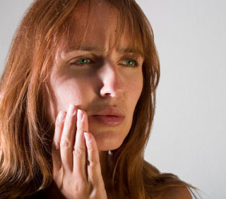 A woman hoping to visit a TMJ dentist appears to be in pain as she lightly touches the side of her jaw.